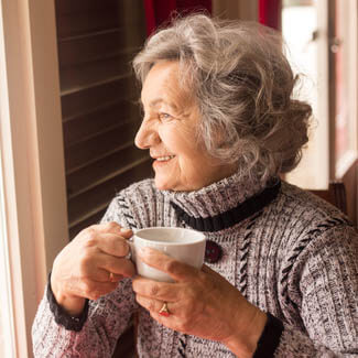 Old lady sat drinking tea coffee looking to right